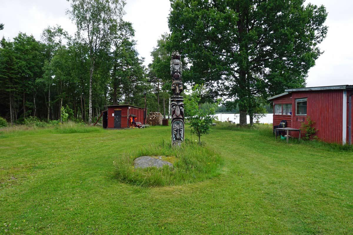 Eine Wiese mit zwei roten kleinen Holzhäuser, ein Matapfahl undBäumen sowie dem See im Hintergrund
