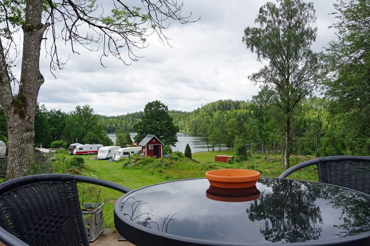 Im Vordergrund sind ein Tisch und zwei Stühle und im Hintergrund wohnmobile, Bäume und ein See